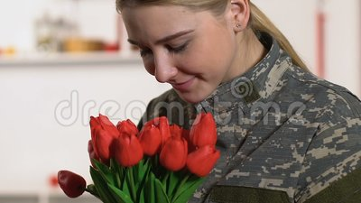 Joli bouquet de tulipes de reniflement d'uniforme militaire de femme, jour de vétérans, patriotisme banque de vidéos