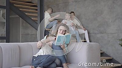 Joli jeune livre de lecture de mère à son fils tandis que le reste de ses enfants de l'adolescence jouant les uns avec les autres banque de vidéos