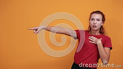 Jolie dame pointant vers la distance, regardant choquée, tenant la main sur la poitrine banque de vidéos