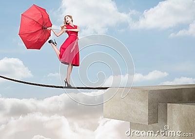 jolie-femme-marchant-sur-une-corde-au-dessus-des-nuages-31669671