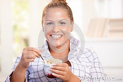 Jolie fille mangeant du yaourt à la maison suivant un régime le sourire