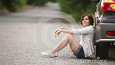 Jolie fille triste s'asseyant sur la route après accident de voiture banque de vidéos