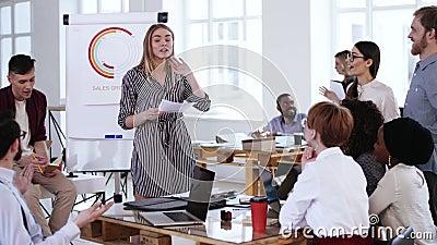 Jolie jeune femme blonde souriante entraîneuse de finances enseignant des travailleurs multiethniques, chef de discussion d'équi clips vidéos