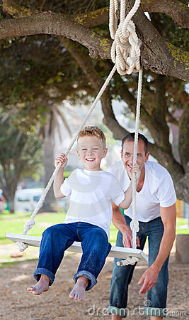 Jolly father pushing his son on a swing