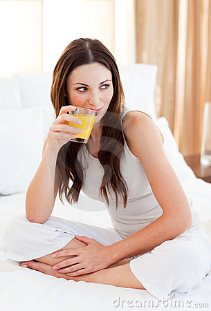 Jolly woman drinking orange juice sitting on bed