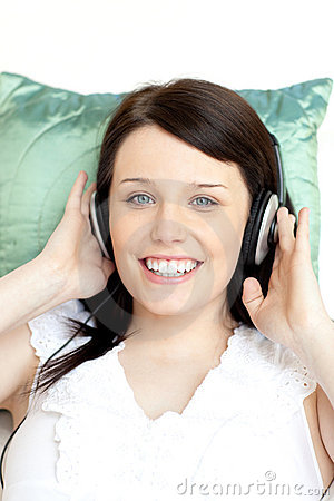 Jolly woman listening music lying on a sofa