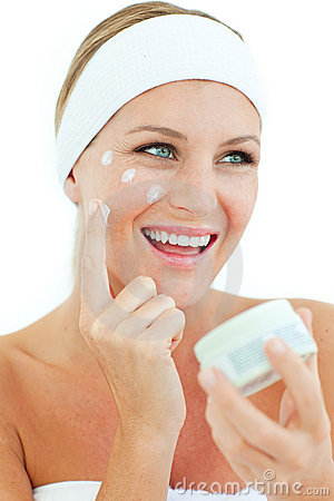 Jolly woman putting cosmetic cream
