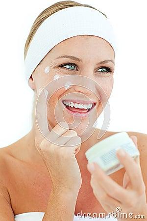 Jolly woman putting cosmetic cream