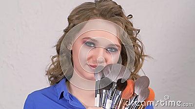 Jong blonde meisje verbergt haar lippen achter make-up penselen Het gezicht is verborgen achter haarkrullen Duidelijk stock video