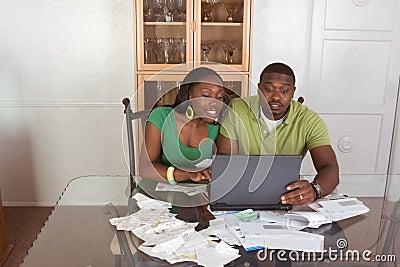 Jong etnisch paar dat rekeningen over Internet betaalt
