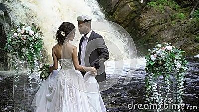 Jong huwelijkspaar die aan ceremonie dichtbij waterval lopen stock footage