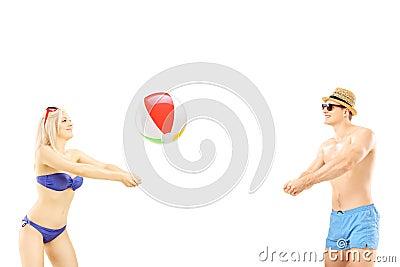 Jong mannetje en wijfje in het swimwear spelen met een strandbal