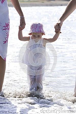Jong meisje dat op strand door ouders wordt gelopen