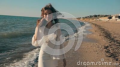 Jong mooi meisje die dichtbij de kust lopen en stock footage