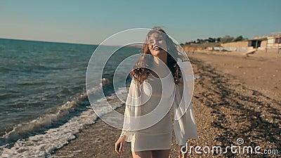 Jong mooi meisje die dichtbij de kust lopen en stock video
