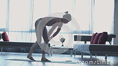 Jong mooi sportief Kaukasisch meisje die yogaposities, asana uitoefenen binnen stock video