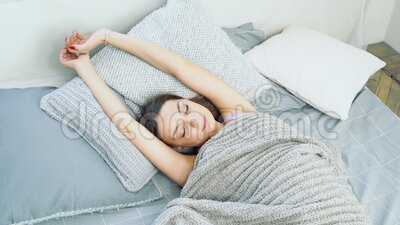 Jonge, aantrekkelijke vrouw die in bed wakker wordt Het begrip rust en gezonde slaap stock video