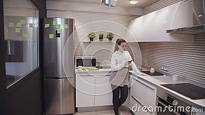 Jonge aantrekkelijke vrouw die telefonisch op internet surft terwijl ze thuis of in een appartement in de keuken staat stock videobeelden