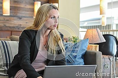 Jonge bedrijfsvrouw die laptop met behulp van