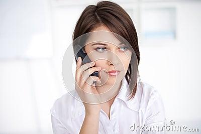 Jonge bedrijfsvrouw die op telefoongesprek spreekt