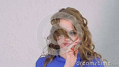 Jonge blonde meid verdraait een haarslot om haar vinger Het gezicht is verborgen achter haarkrullen stock footage