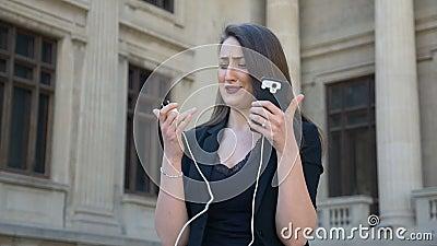 Jonge boze en bezorgde vrouw die terwijl haar telefoondraaien weg wegens geloste lage batterij in de stad schreeuwen stock videobeelden