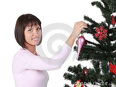 Jonge brunette die de Kerstboom verfraait