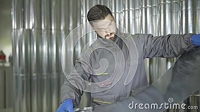 Jonge caucasiaanse mannelijke werknemer die op de achtergrond staat van buizen van metaal die klaar zijn voor gebruik en die het  stock footage