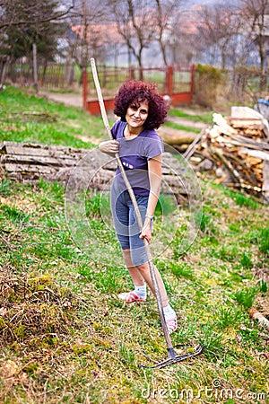Jonge dame met de harklente die de tuin schoonmaakt