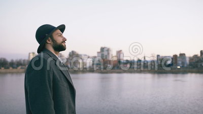 Jonge gebaarde toeristenmens in hoed en laag het letten op cityscape en het dagdromen terwijl status op rivieroever stock footage