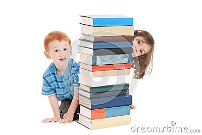 Jonge geitjes die achter stapel boeken verbergen
