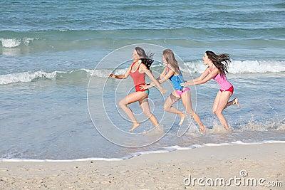 Jonge geitjes, tienerjaren die op strandvakantie lopen