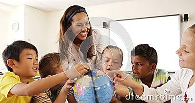 Jonge geitjes van de leraars de bijwonende school in lezingsbol in klaslokaal stock footage