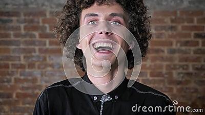Jonge gelukkige mens met krullend camera bekijken en haar die, bakstenen muurachtergrond lachen stock video