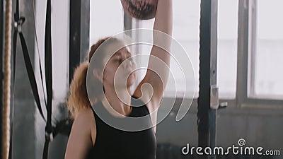 Jonge, geschikte, witte, rode, blanke vrouw die zwaar kettlebelgewicht optilt in langzame beweging van de draaikolk, actieve leve stock footage