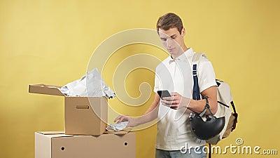 Jonge glimlachende bezorger met geïsoleerde dozen stock videobeelden