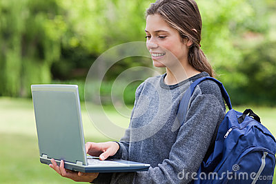 Jonge glimlachende vrouw die haar laptop houdt