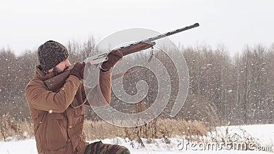 Jonge jager wees op zijn wapen in de vogel stock videobeelden