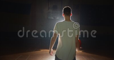 Jonge Kaukasische basketbalspeler die zich klaarmaakt om terug te keren naar de donkere donkere silhouette van licht Vertrouwen s stock footage