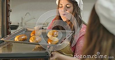 Jonge Kaukasische moeder met aangename glimlach, die verse gebakken broodjes uit de oven neemt en op warme koekjes blaast Vrouw stock footage