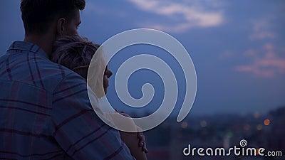 Jonge kerel die zacht zijn meisje koesteren door schouders die haar verwarmen bij zonsondergang stock video