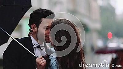 Jonge knappe gebaarde man in een elegant kostuum en uiterst kleine aantrekkelijke vrouw in vrijetijdskleding met korenbloemboeket stock videobeelden