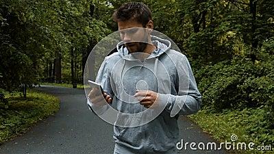 Jonge krachtige agent buiten in het park van de de herfstaard met telefoon stock videobeelden