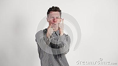 Jonge man caucasiaans uiterlijk, in zijn hemd laat zijn emoties van vreugde en overwinning zien Op een witte achtergrond stock footage
