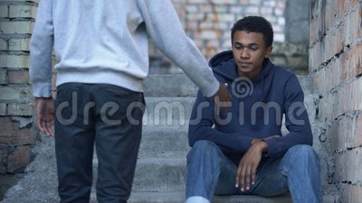 Jonge man die de hand uitsteekt naar trieste vrienden die trappen zitten, vriendschapsondersteuning stock video