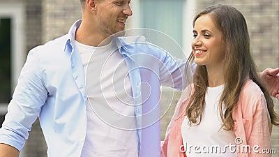 Jonge man en vrouw die zich te koop stellen, tekenen zich in de woningtuin aan, jonge familieherplaatsing stock footage