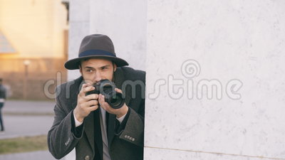 Jonge mannelijke spionagent hoed dragen en laag die misdadige mensen fotograferen en achter de muur verbergen stock video