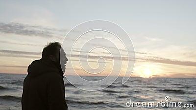 Jonge mens die in de kust van het alleen overzees lopen en op de golven kijken Mannetje die van de zonsondergang op het strand ge stock video