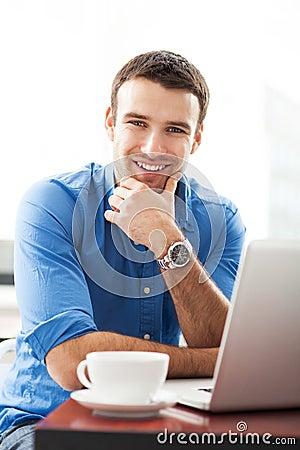 Mens die laptop in koffie met behulp van