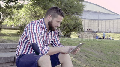 Jonge mens het doorbladeren tablet, die op treden zitten schuifschot stock videobeelden